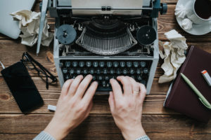 hands-creating-content-on-a-typewriter