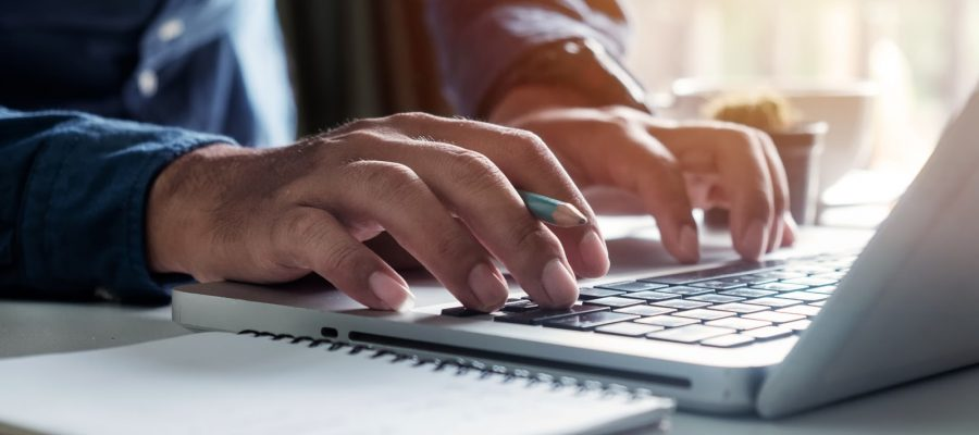 A man writing content on a computer.