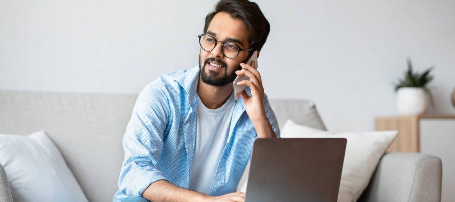 Happy Man On Laptop & Phone Getting Good Customer Service